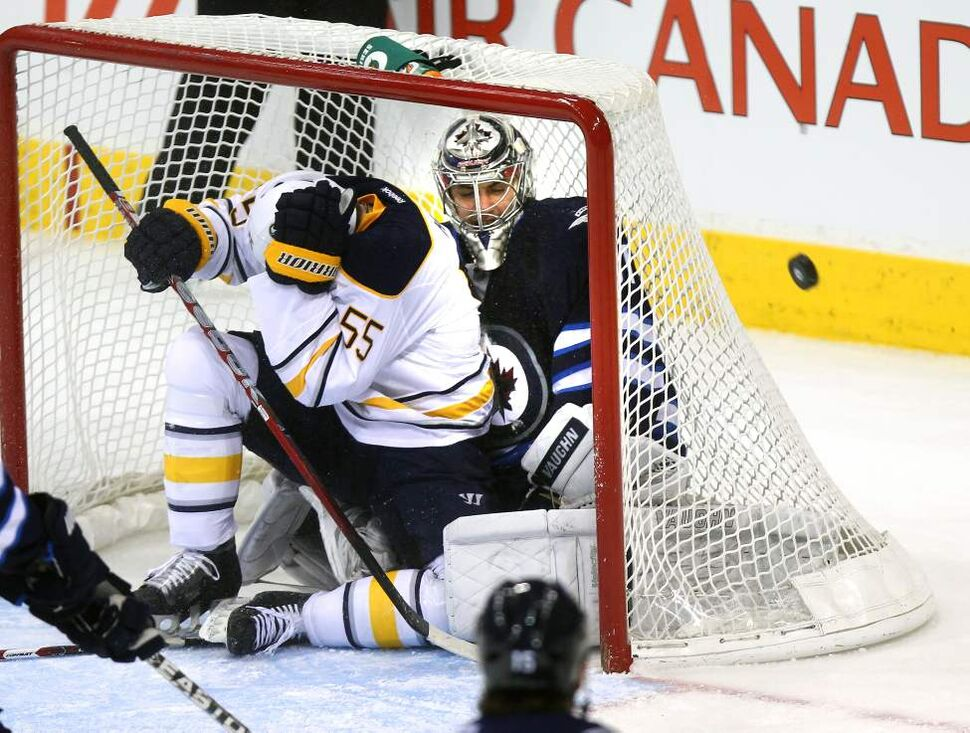Buffalo Sabres Jochen Hecht covers up after finding himself the target of his own team inside the Winnipeg Jets net with Ondrej Pavelec during second-period action Thursday.  Hecht drew a two-minute interference call on the play. January 18, 2012  (Phil Hossack / Winnipeg Free Press)
