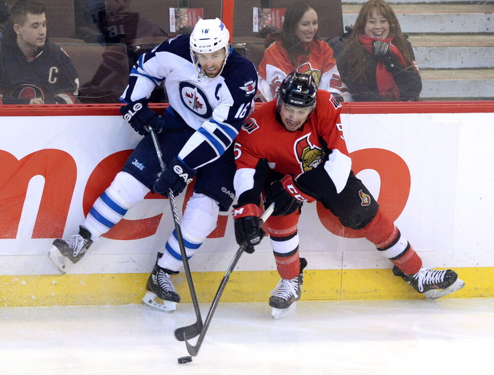 Ottawa Senators' Cody Ceci, right, and Winnipeg Jets' Adrew Ladd fight for the puck during first period NHL hockey action in Ottawa Thursday. (Sean Kilpatrick / The Canadian Press)