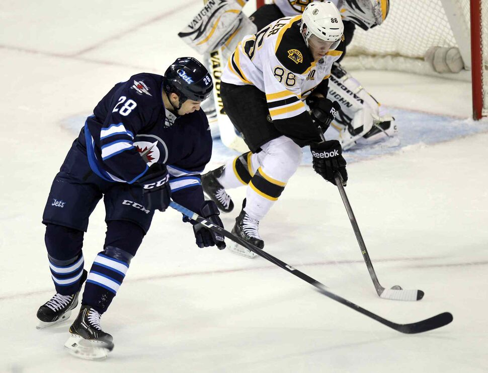 Winnipeg Jets' Patrice Cormier and Boston Bruins' Kevan Miller battle for the puck in the first period of Thursday's game. (Phil Hossack / Winnipeg Free Press)