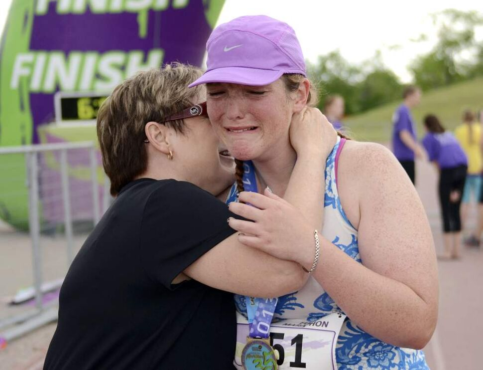 Jayne Mullen cries and hugs her mother after finishing her marathon at the last minute at 12:59 with a time of 5:59:00. (OLIVER SACHGAU / WINNIPEG FREE PRESS)