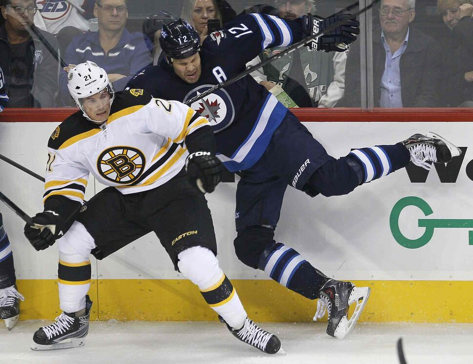 Boston Bruins' Loui Eriksson (left) takes out Winnipeg Jets' Olli Jokinen during the first period. (JOHN WOODS / THE CANADIAN PRESS)