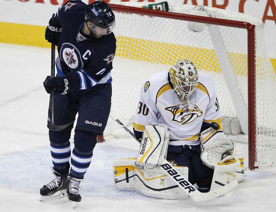 Nashville Predators' goaltender Carter Hutton (30) gets his glove on the deflection from Winnipeg Jets' Andrew Ladd (16) during the first period. (JOHN WOODS / WINNIPEG FREE PRESS)