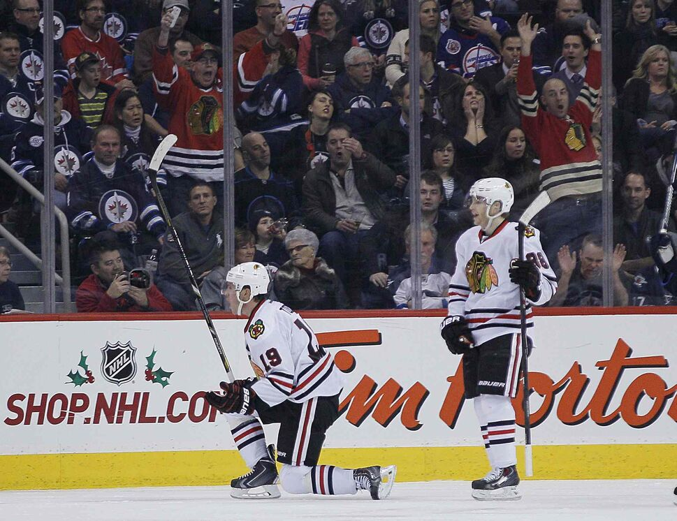 Jonathan Toews (left) and Patrick Kane (88) celebrate Toews' goal against the Winnipeg Jets during the second period. (JOHN WOODS / THE CANADIAN PRESS)