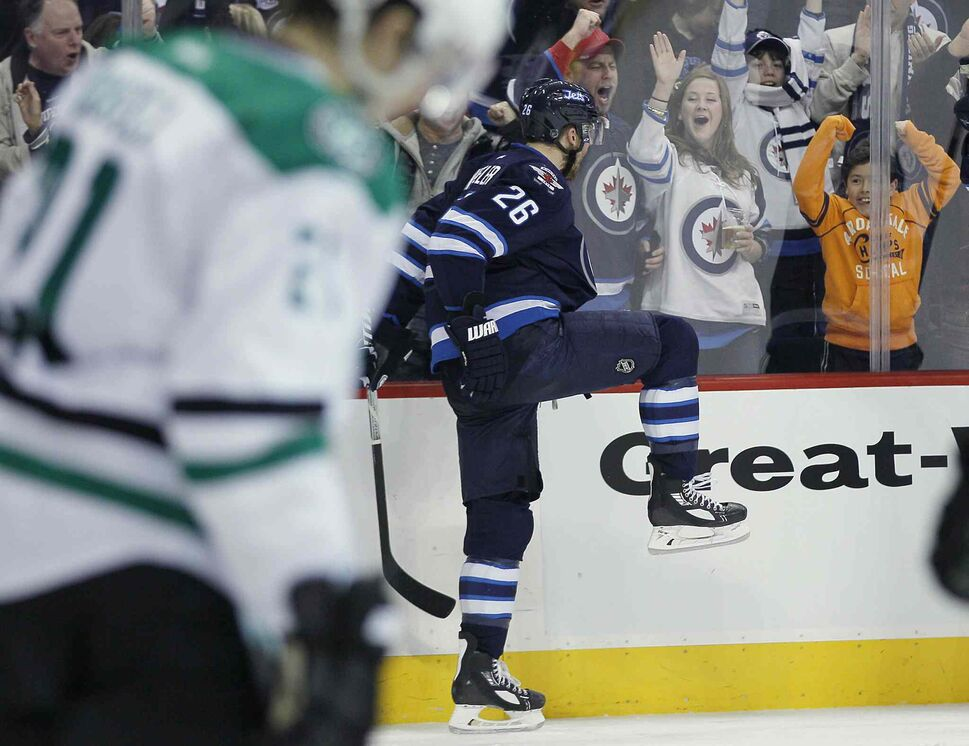 Blake Wheeler (right) celebrates his second goal against the Dallas Stars as Antoine Roussel skates by during the second period. (JOHN WOODS / THE CANADIAN PRESS)