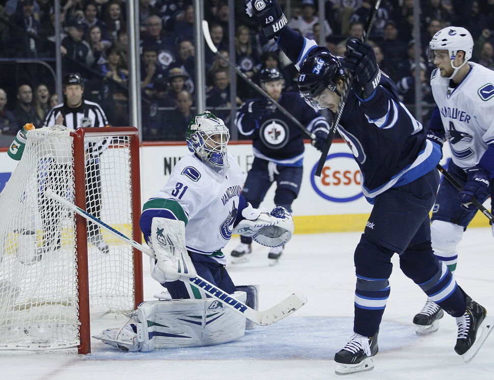 Winnipeg Jets' Michael Frolik (67) celebrates Andrew Ladd's (16) goal on the Vancouver Canucks as Alexander Edler (23) looks on during second period NHL action. (JOHN WOODS / THE CANADIAN PRESS)
