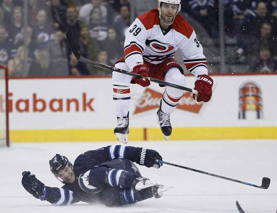 Carolina Hurricanes' Patrick Dwyer (39) leaps over Winnipeg Jets' Matt Halischuk (15) during second period NHL action in Winnipeg. (JOHN WOODS / THE CANADIAN PRESS)