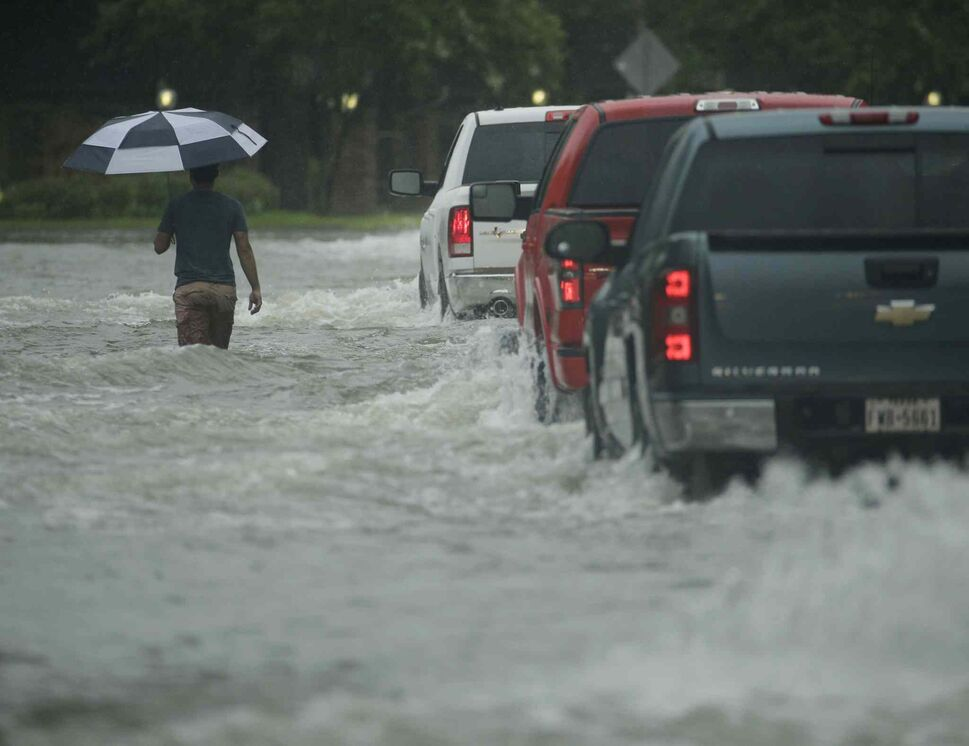 A pedestrian crosses a street inundated by floodwaters from Tropical Storm Harvey on Sunday, Aug. 27, 2017, in Houston, Texas. (Charlie Riedel / The Associated Press)