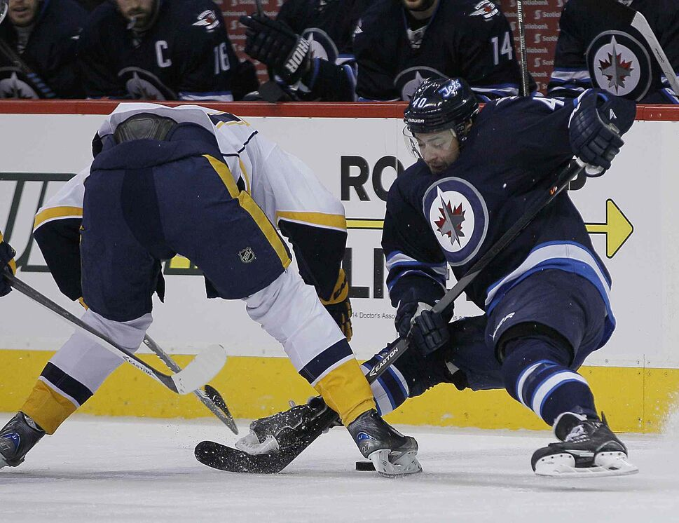 Winnipeg Jets' Devin Setoguchi (40) fights for the puck with Nashville Predators' Patric Hornqvist (27) during the second period of Tuesday's game at MTS Centre. (John Woods / Winnipeg Free Press)