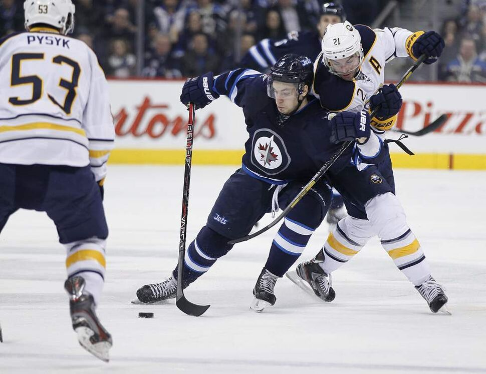 Winnipeg Jets' Alexander Burmistrov (8) fights to bust around Buffalo Sabres' Drew Stafford (21) during second period NHL action in Winnipeg. 