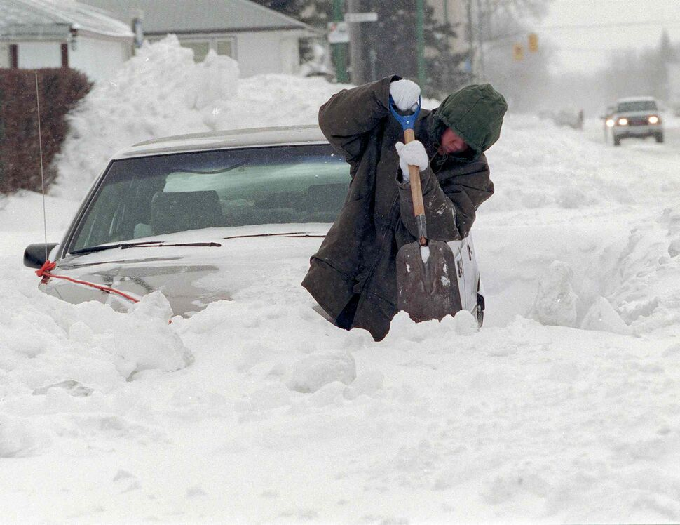The snowfall was not merely deep - it was lead-heavy. It would melt into millions of cubic feet of water. Plaridel Orcullo digs out on Mountain Avenue after the storm. (Wayne Glowacki / Winnipeg Free Press files)