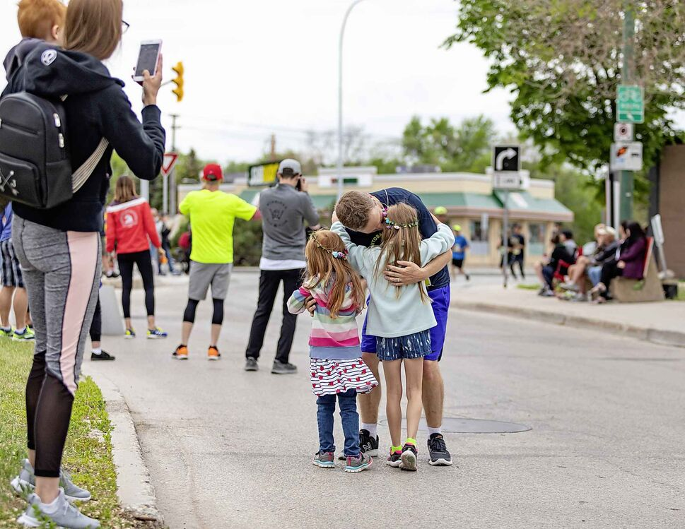 Colin Jones gets some encouragement from his family, (from left) wife Jenna with Lachlan, 2, Tessa, 4, and Nicola, 7, during the half marathon. Sasha Sefter / Winnipeg Free Press  190616 - Sunday, June 16, 2019.