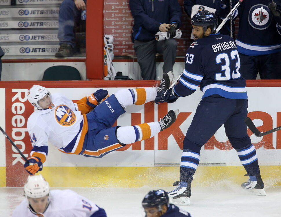 New York Islanders' Thomas Hickey (14) flies after being checked by Winnipeg Jets' Dustin Byfuglien (33) during the first period.  (Trevor Hagan / THE CANADIAN PRESS)