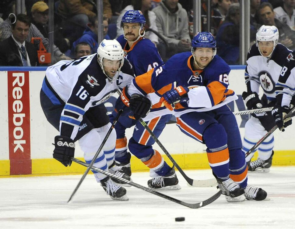 Winnipeg Jets captain Andrew Ladd (left) cuts in on New York Islanders forward Josh Bailey (centre right) in the second period. (Kathy Kmonicek / The Associated Press)