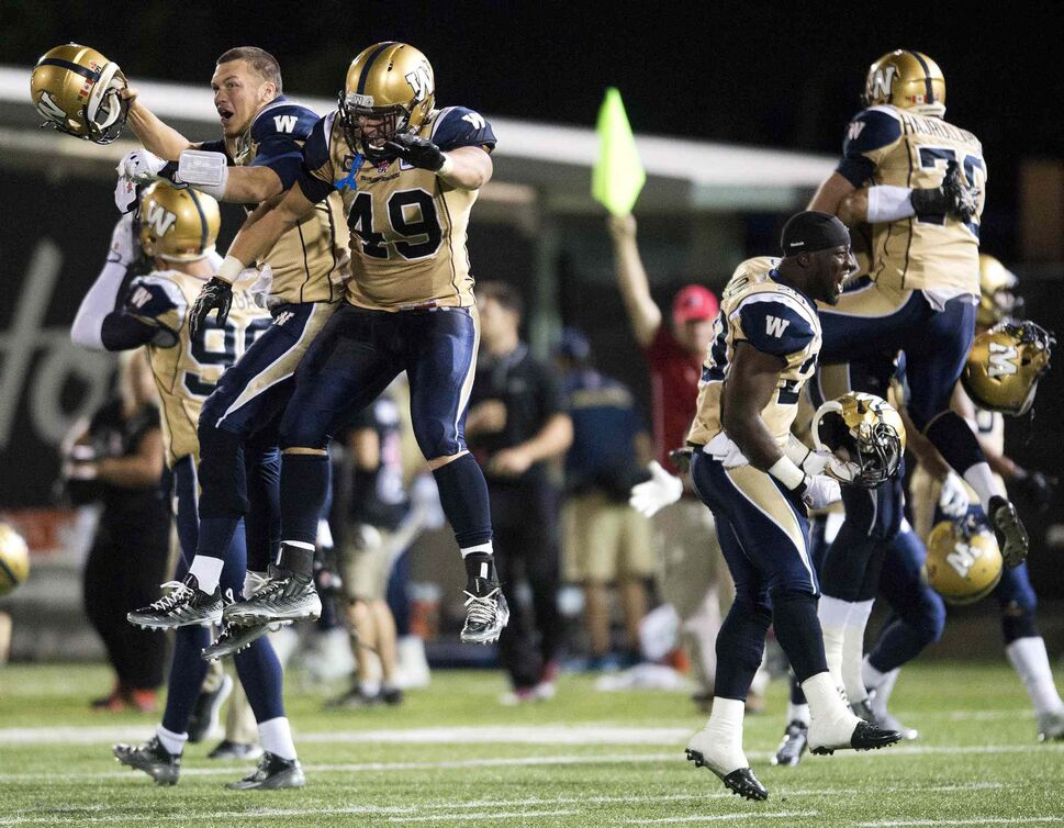 Winnipeg Blue Bombers' Robert Marve, left, and Mike Cornell, right, celebrate after defeating the Hamilton Tiger-Cats. (Nathan Denette / The Canadian Press)