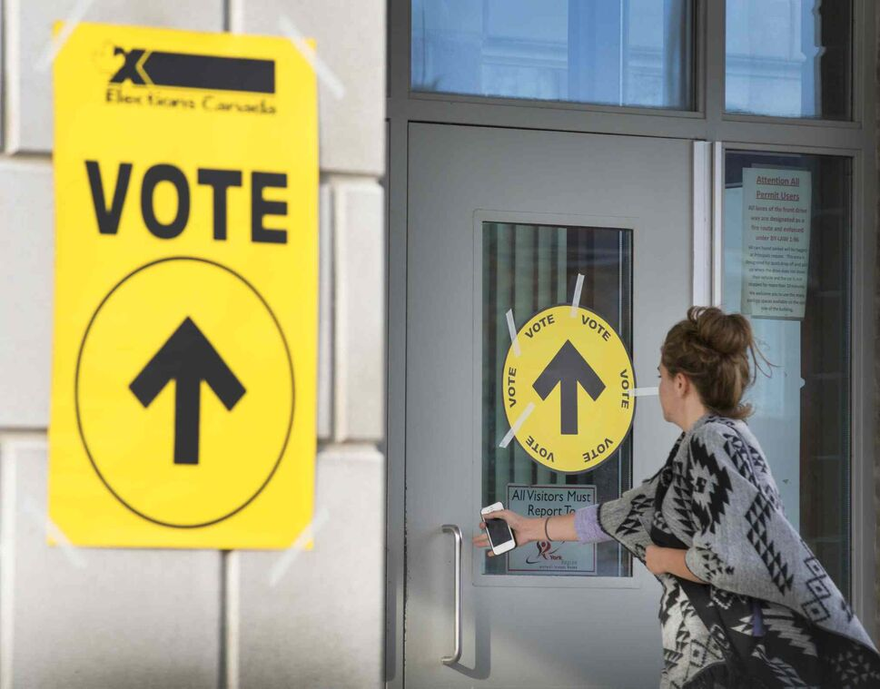 A woman enters Maple High School in Vaughan, Ont., to cast her vote in the Canadian federal election on Monday, Oct. 19, 2015.  THE CANADIAN PRESS/Peter Power (CP)
