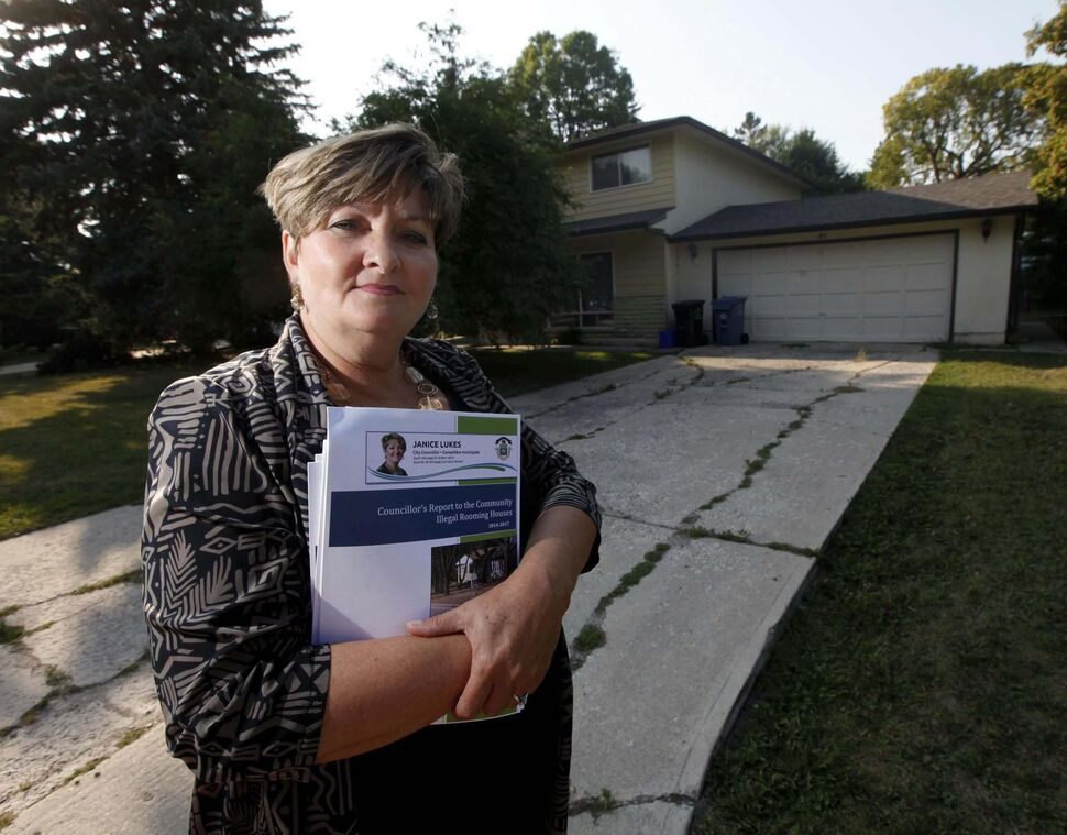 Coun. Janice Lukes stands in front of a Thatcher Drive house used as an illegal rooming house, holding a report on the issue. (PHIL HOSSACK / WINNIPEG FREE PRESS)