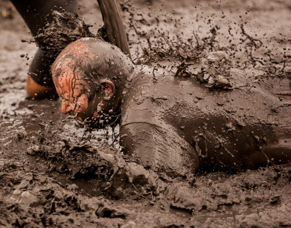 A Dirty Donkey Mud Run participant is covered in muddy water near the finish line of the Dirty Donkey Mud Run Saturday morning.  (Melissa Tait / Winnipeg Free Press)