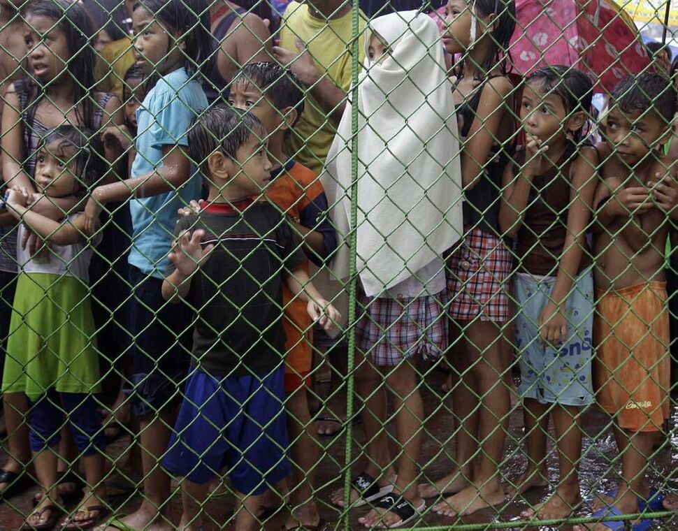 Young evacuees look from behind a fence at a school converted into a temporary evacuation center in Marikina City, east of Manila, Philippines, on Wednesday Aug. 8, 2012. Widespread flooding that killed at least 11 people, battered a million others and paralyzed the Philippine capital began to ease Wednesday as cleanup and rescue efforts focused on a large number of distressed residents, some still marooned on their roofs.  AP Photo / Aaron Favila