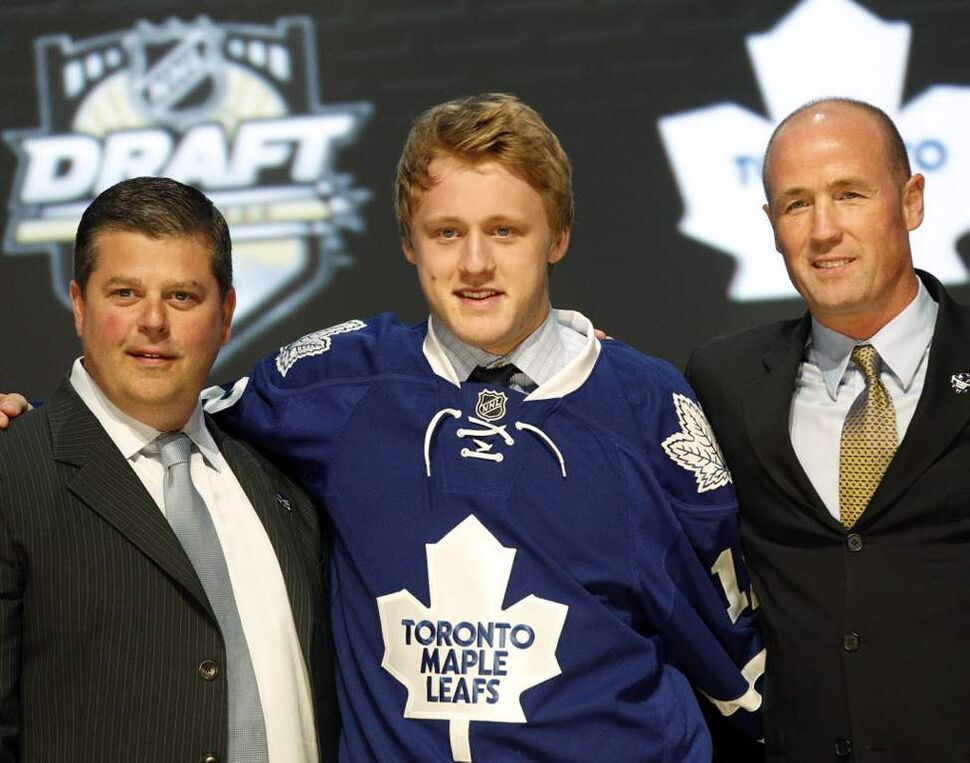 Morgan Rielly, centre, a defenceman, stands with officials from the Toronto Maple Leafs after being chosen fifth overall in the first round of the NHL hockey draft, in Pittsburgh. (AP Photo/Keith Srakocic)