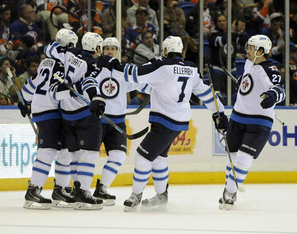 Winnipeg Jets' Mark Stuart (second from left) celebrates his goal with teammates in the second period. (Kathy Kmonicek / The Associated Press)