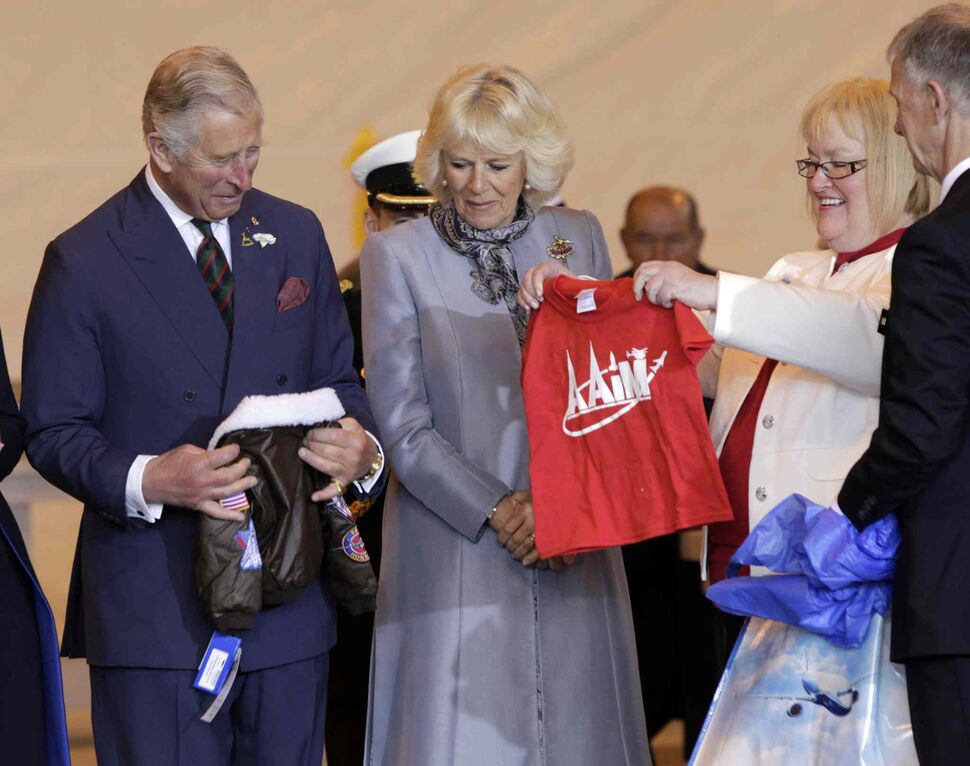 At right, Barb Bowen presents Prince Charles and Camilla, Duchess of Cornwall a flight jacket and a t-shirt for Prince George at the ceremony in the Stevenson Hangar Wednesday morning.    (Wayne Glowacki / Winnipeg Free Press)