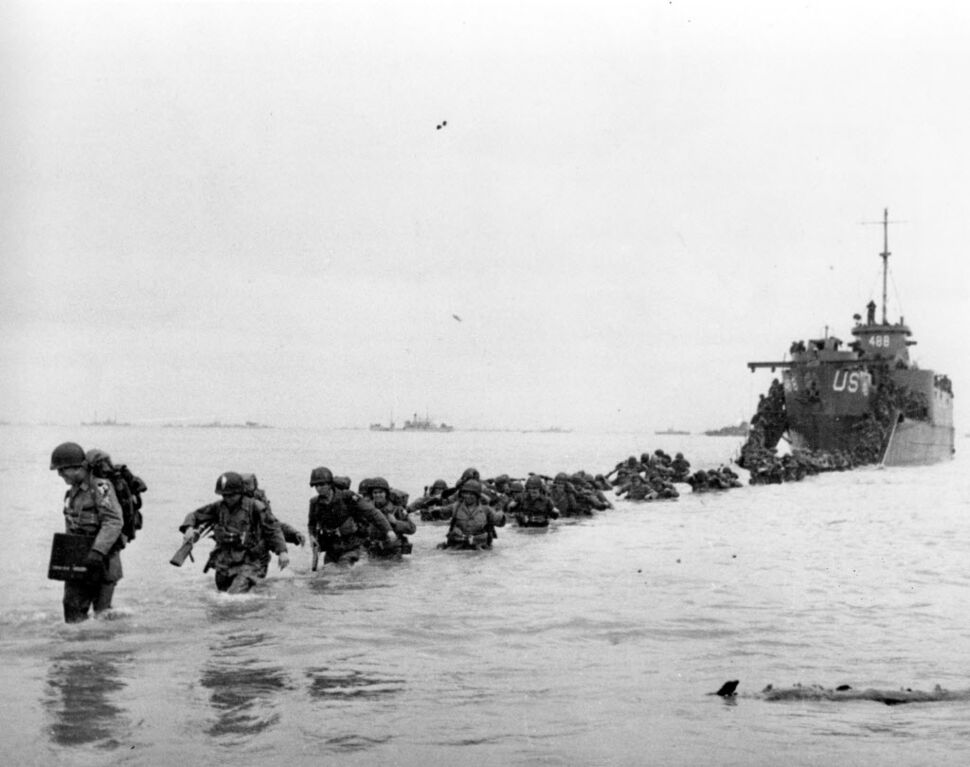 U.S. reinforcements wade through the surf from a landing craft in the days following D-Day and the Allied invasion of Nazi-occupied France at Normandy in June 1944 during World War II.  From the first sketchy German radio broadcast to the distribution of images filmed in color, it has taken decades for the full story of the D-Day invasion to come out.  Photographs by Robert Capa, who was embedded with U.S. troops on Omaha Beach, took more than an week to reach American news.   (Bert Brandt / The Associated Press files )