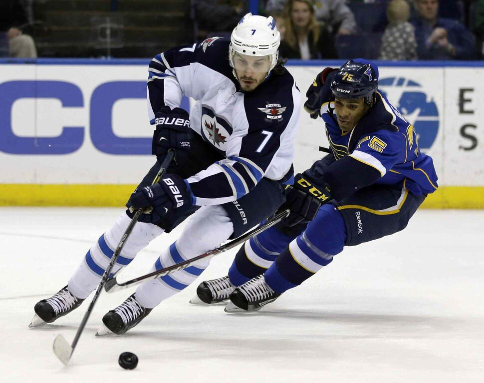 Jets defenceman Keaton Ellerby controls the puck as Blues forward Ryan Reaves defends during the second period. (JEFF ROBERSON / THE ASSOCIATED PRESS)