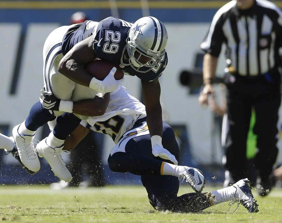 San Diego Chargers cornerback Johnny Patrick (right) upends Dallas Cowboys running back DeMarco Murray during the Chargers 30-21 win Sunday in San Diego. (Gregory Bull / The Associated Press)