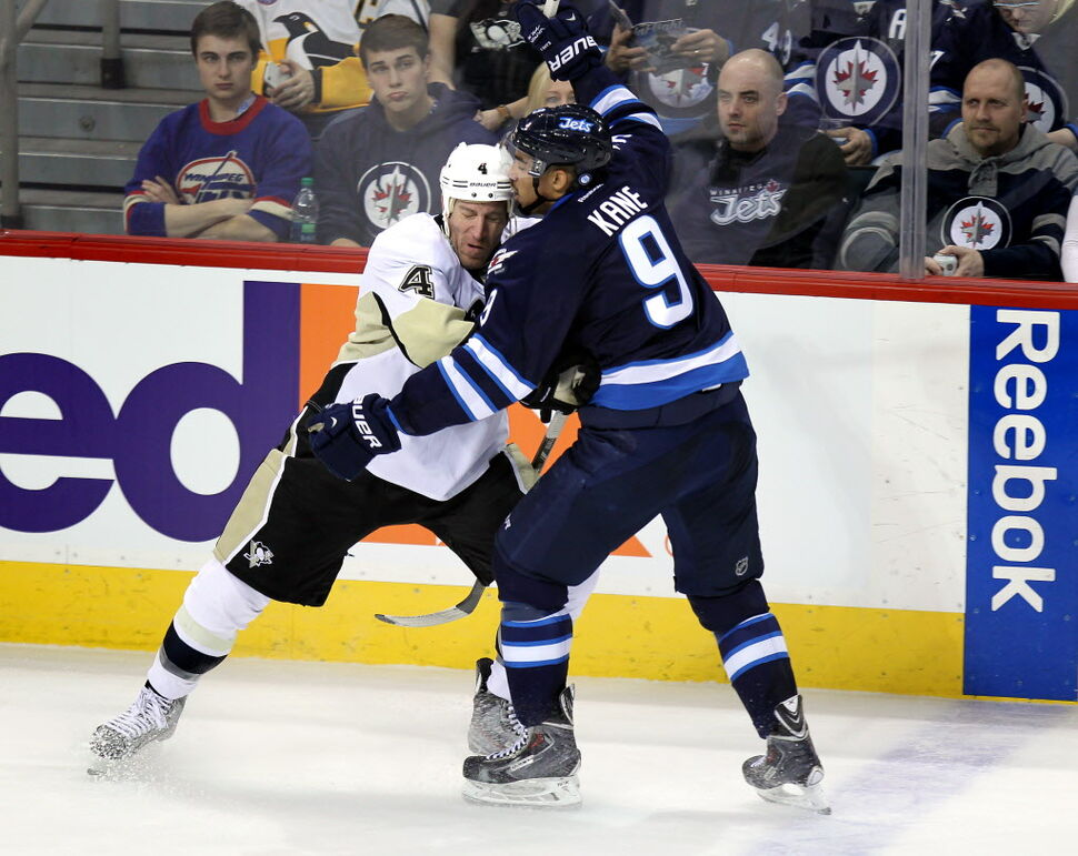Pittsburgh Penguin defenceman Rob Scuderi (4) ties up Evander Kane in front of a sombre crowd.  (Phil Hossack / Winnipeg Free Press)