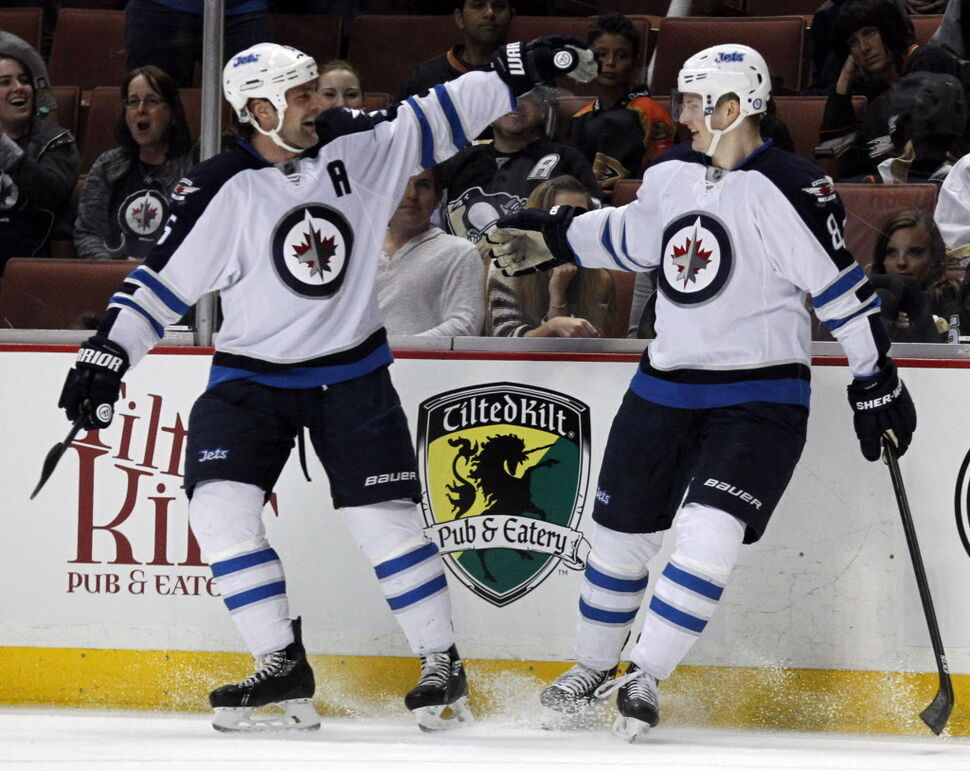 Winnipeg Jets' defenseman Mark Stuart, left, celebrates a first-period goal by defenseman Jacob Trouba, right, during Monday's game. (Alex Gallardo / The Associated Press)