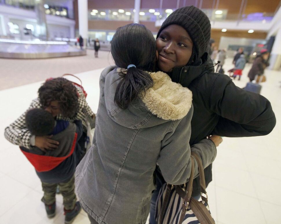 16-year-old Naomi (right) is welcomed to Winnipeg by her sister Alice. (Phil Hossack / Winnipeg Free Press)