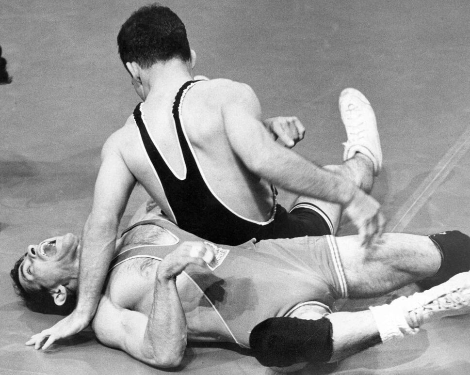 Canada's Peter Michienzi writhes in pain as his opponent, Dick Sofman of the USA, applies pressure from the other side in a wrestling match.   (Winnipeg Free Press Files)