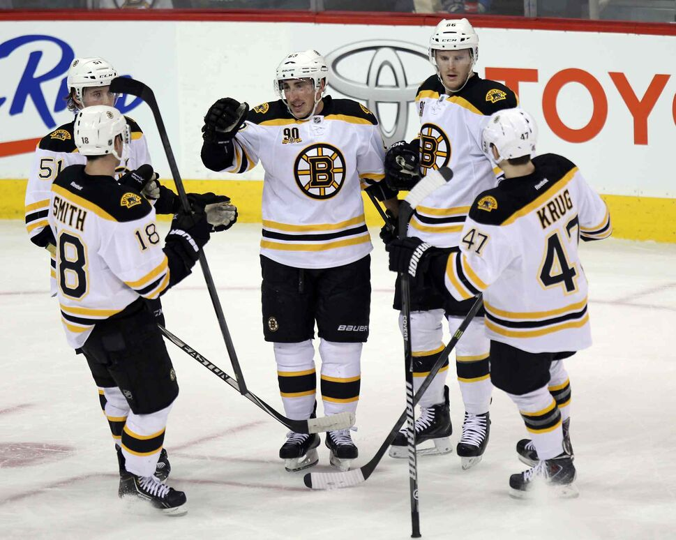 Boston Bruin linemates congratulate #63 Brad Marchand (centre) for scoring the Bruins' opener in the first period of Thursday's game. (Phil Hossack / Winnipeg Free Press)