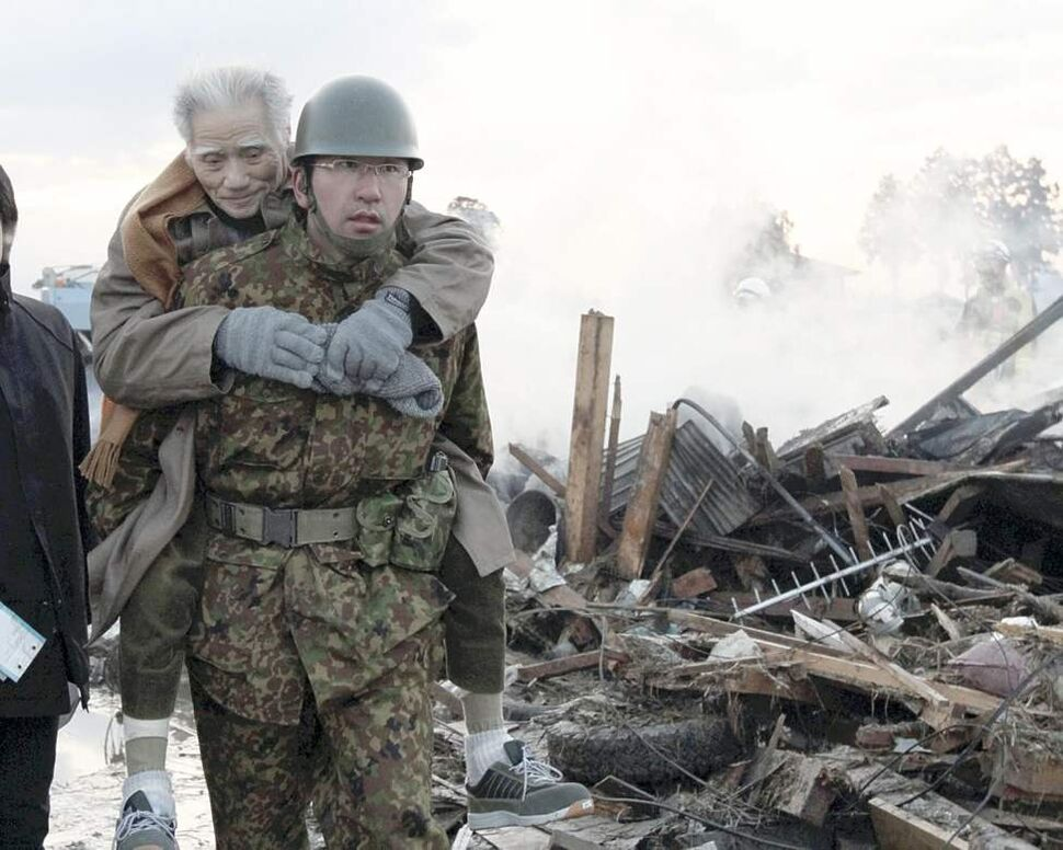 An elderly man is being carried by Self-Defense Force member in the tsunami-torn Natori city, Miyagi Prefecture, northern Japan, Saturday morning, March 12, 2011, one day after strong earthquakes hit the area. (AP Photo/The Yomiuri Shimbun, Yasushi Kanno)