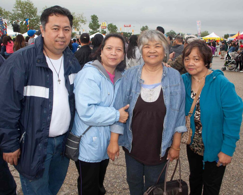 The Manitoba Filipino Street Festival didn't let the rain dampen its annual parade and party at Garden City Shopping Centre on Aug. 22, 2015. Pictured, from left, are Fernando Celestino, Norita Celestino, Mila Comiso and Beth Ledesma. (JOHN JOHNSTON FOR THE WINNIPEG FREE PRESS)