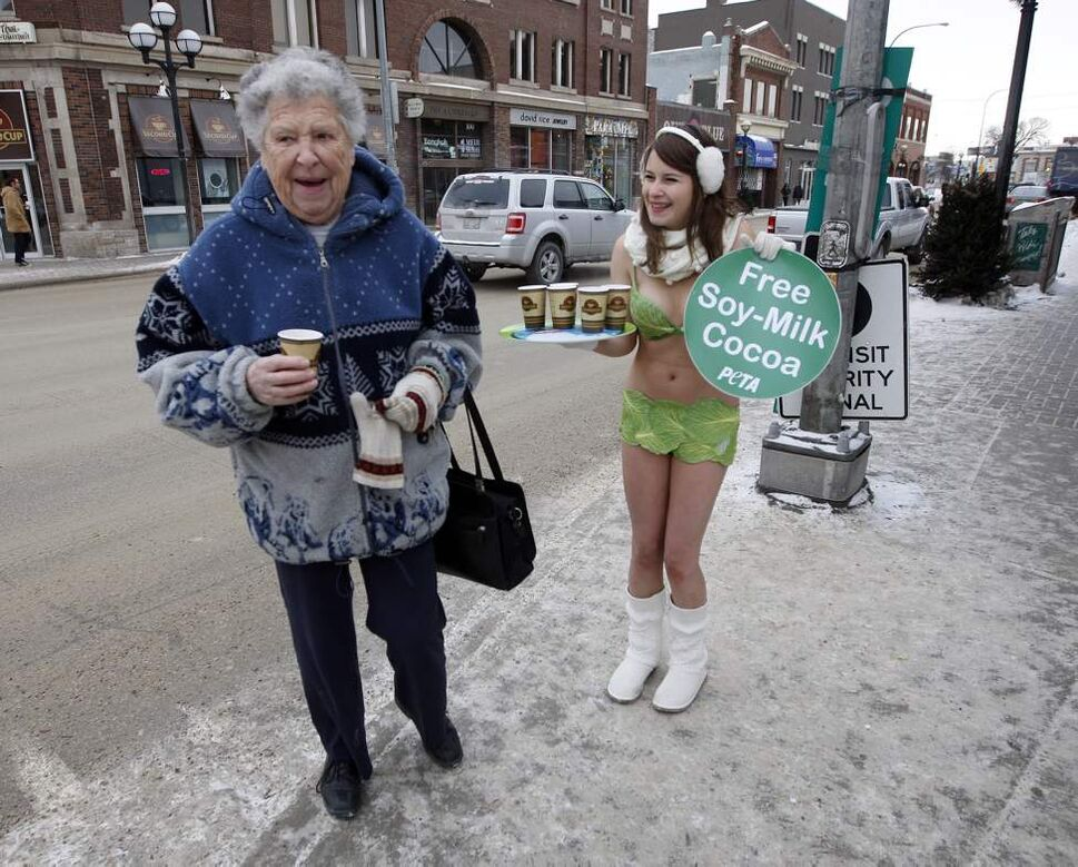 """A bundled up Pattie Page has a laugh and a free cup of hot soy-milk cocoa given out by PETA's Emily Lavender. """"Sexy Lettuce Lady"""" sported a bikini and served hot drinks in Osborne Village in -12 degree temperatures to encourage passerbys to go vegan. January 10,  2011"""