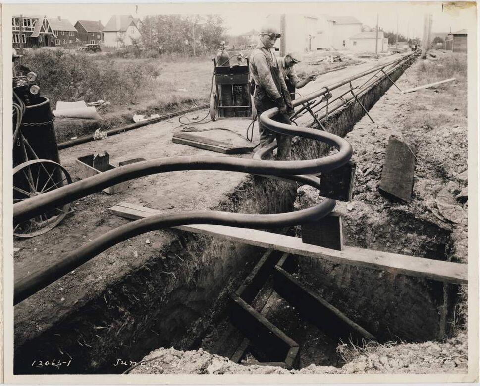 A crew lays steam pipes, central steam expansion curves in the North End of Winnipeg, June 2, 1931.