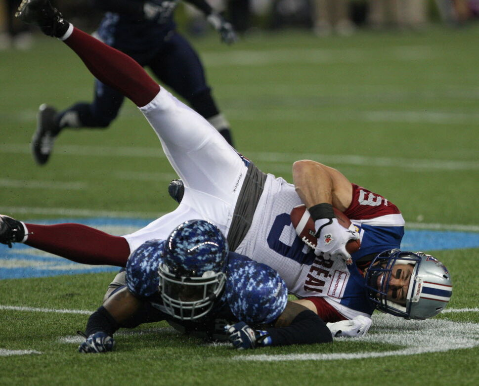 Winnipeg Blue Bombers Bruce Johnson, bottom, low tackles Montreal Alouettes Eric Deslauriers during the first half Friday night.  (JOE BRYKSA / WINNIPEG FREE PRESS)
