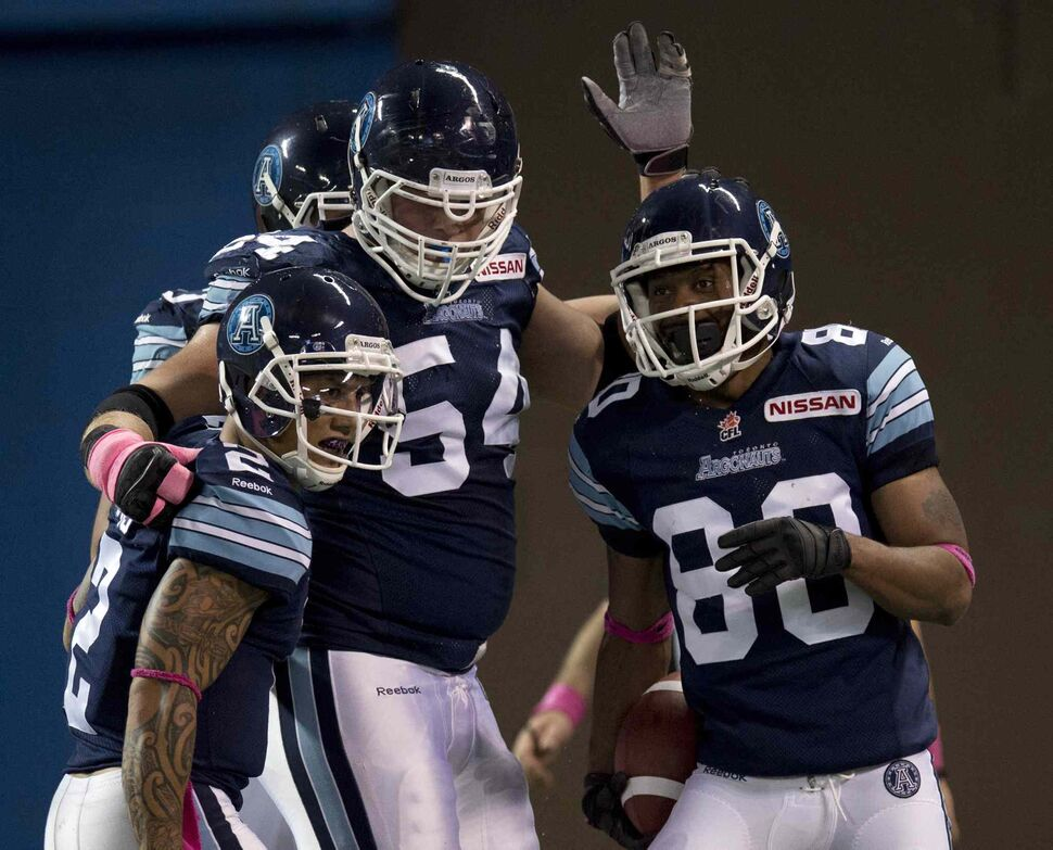 Toronto Argonauts wide receiver Romby Bryant (right) is congratulated by teammates Chad Owens (left) and Chris Van Zeyl after hauling in a touchdown pass against the Winnipeg Blue Bombers during the first half. (Frank Gunn / The Canadian Press)