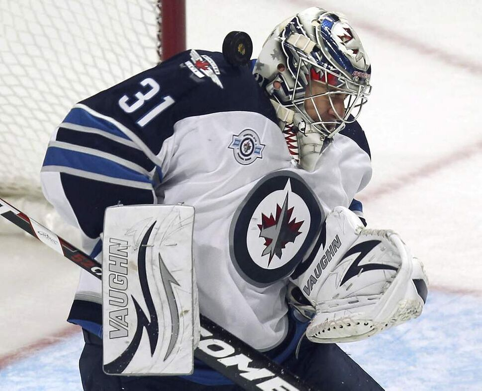 Winnipeg Jets goaltender Ondrej Pavelec gets the puck in the helmet during first period NHL action Thursday night against the Chicago Blackhawks at the United Centre in Chicago. October 13, 2011 (JOE BRYKSA / WINNIPEG FREE PRESS)