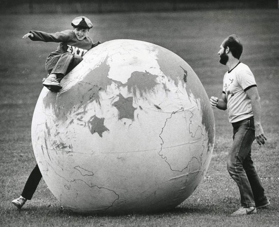Joel Bailey, 10, finds he has to fight the forces of gravity to complete his world tour of continents marked on the earth ball at the Winnipeg Folk Festival. John Radcliffe monitors the young traveller's progress. July 12, 1986. (PHIL HOSSACK / WINNIPEG FREE PRESS)