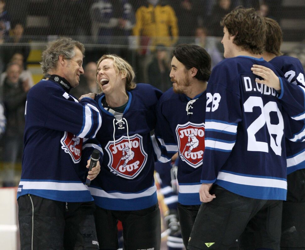 Canadian rock star Jim Cuddy, left, has a laugh with Amanda Rheaume as they and others on Team Rockers sing 'O Canada' before the 11th annual Juno Cup at MTS iceplex Friday night. (Joe Bryksa / Winnipeg Free Press)