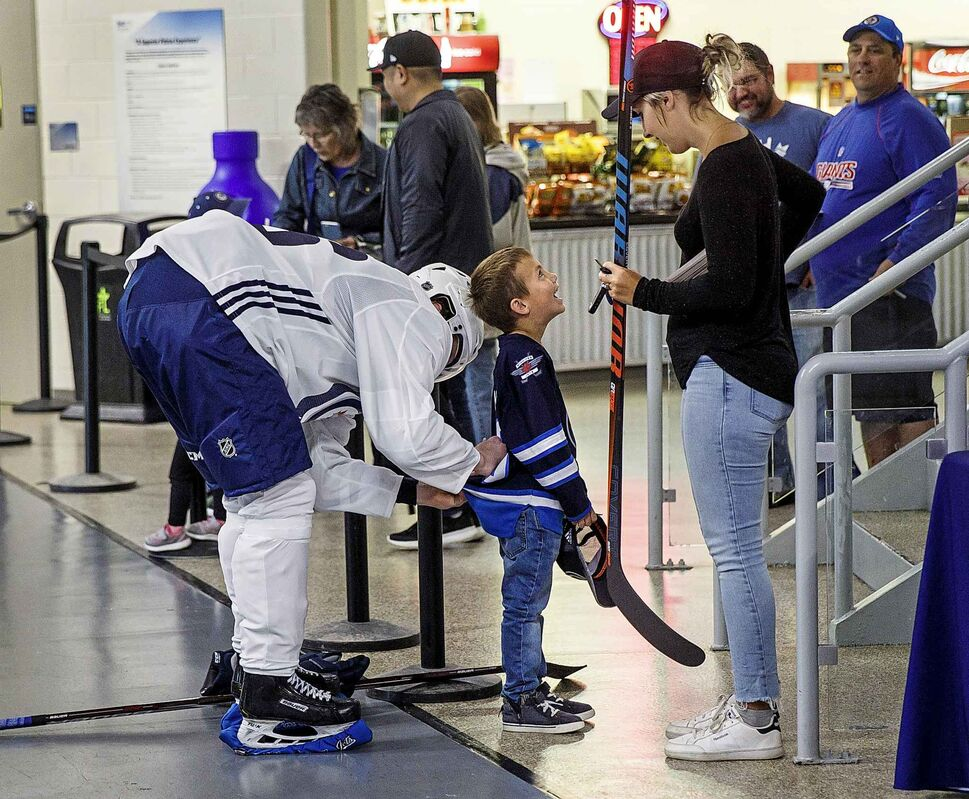 MIKE DEAL / WINNIPEG FREE PRESS Winnipeg Jets' first round draft pick, Ville Heinola, signs six-year-old Jaxx Kornelsen's jersey while his mother, Tiffany, watches during development camp the Bell MTS Iceplex on June 24.
