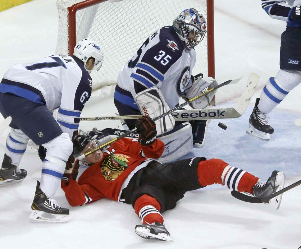 Jets goalie Al Montoya (35) makes a save with Blackhawks captain Jonathan Toews crowding the net. (Charles Rex Arbogast / The Associated Press)