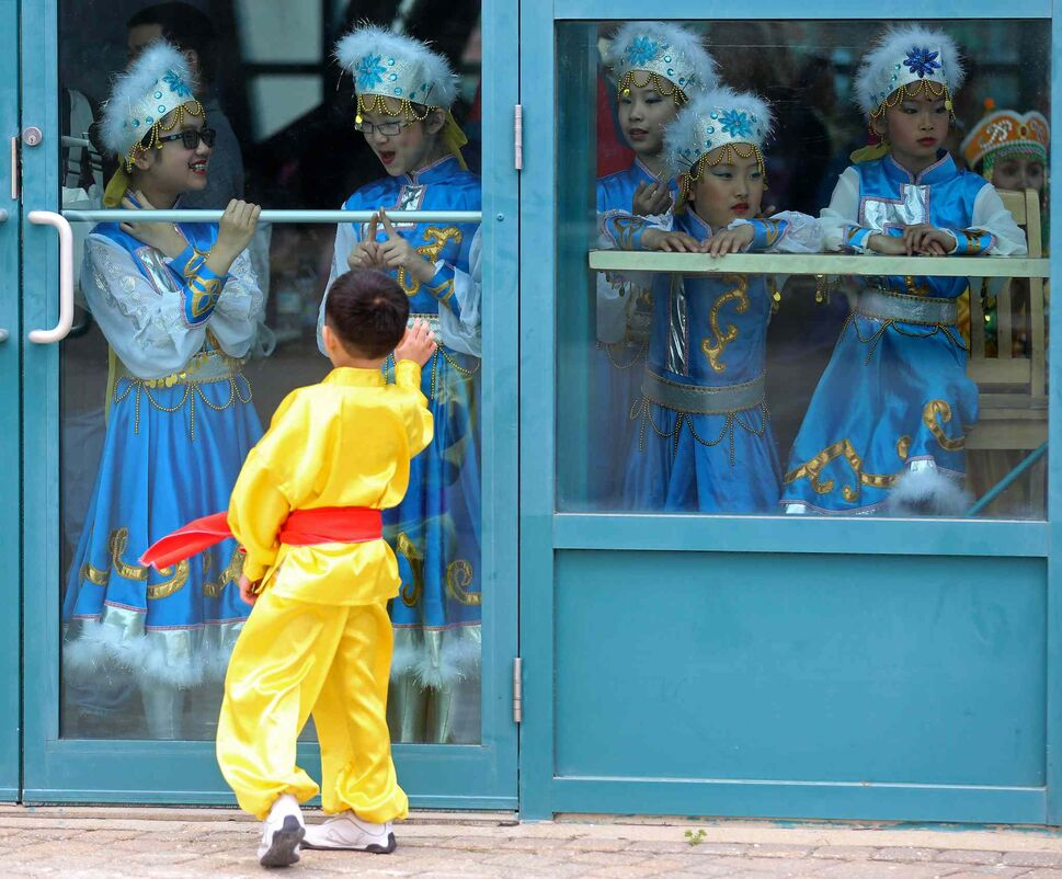 A young performer from the Great Wall Performing Arts school teases another group of performers prior to taking the stage during Asian Heritage Month celebrations at The Forks, Sunday. (TREVOR HAGAN / WINNIPEG FREE PRESS)