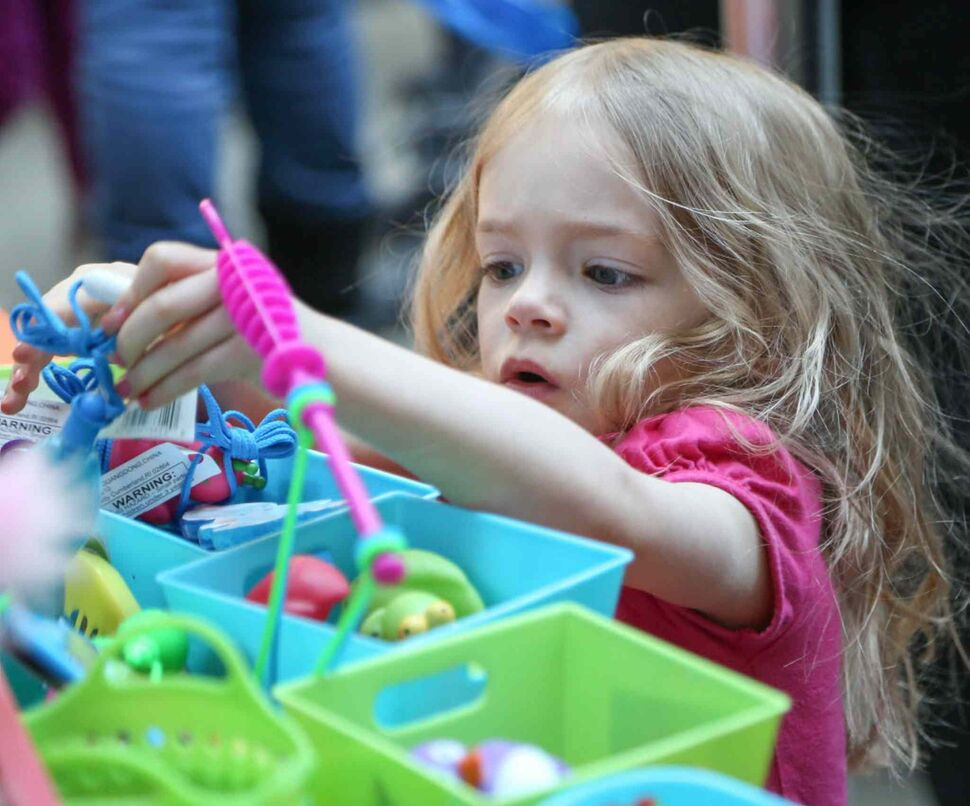 Lucy Sayre, 2, can't decide which colourful toy she likes more at the Forks on Tuesday. (Crystal Schick / Winnipeg Free Press)