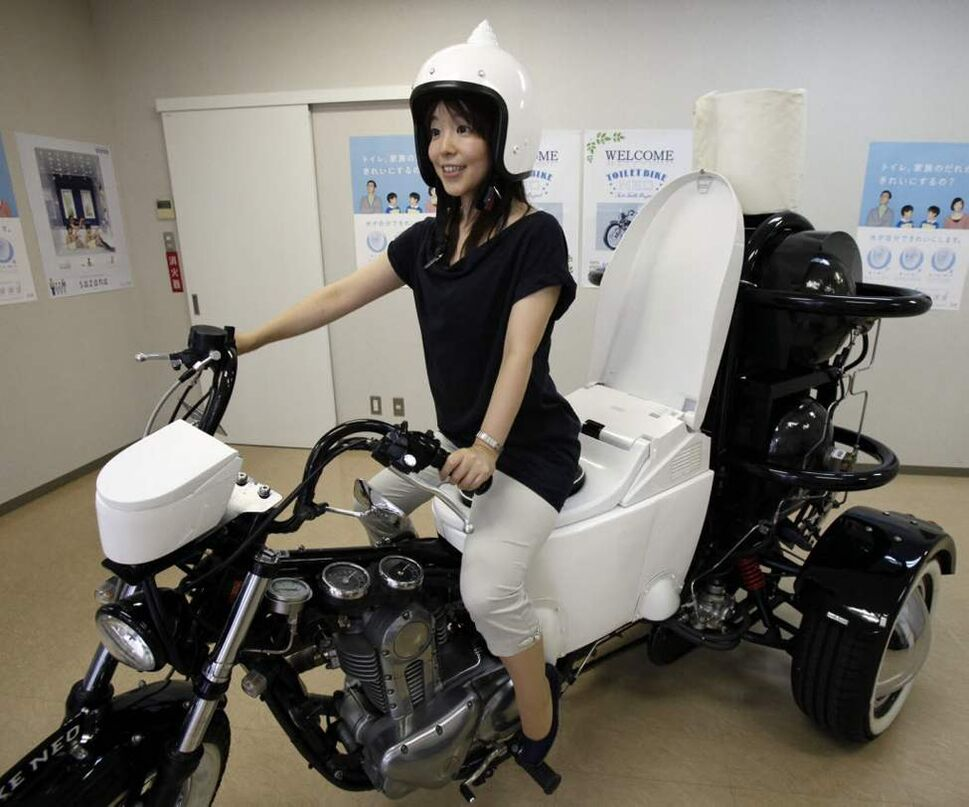 "Japanese toilet maker TOTO employee Akiko Matsuyama gets on a ""Toilet Bike Neo"" displayed at its showroom in Fujisawa. TOTO rolled out the eco-friendly three-wheel 250cc motorcycle with a specially customized toilet-shaped seat that runs on bio-fuel from the discharge of livestock or waste water. (AP Photo/Koji Sasahara)"