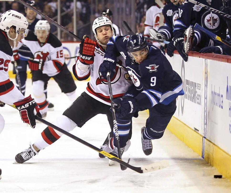 Winnipeg Jets' Evander Kane (9) fights to get to the puck as the New Jersey Devils' Cam Janssen (25) pulls him down onto the ice during second period action at MTS Centre. The New Jersey Devils won the game 2 - 1. January 14, 2012. (Ruth Bonneville /  Winnipeg Free Press)
