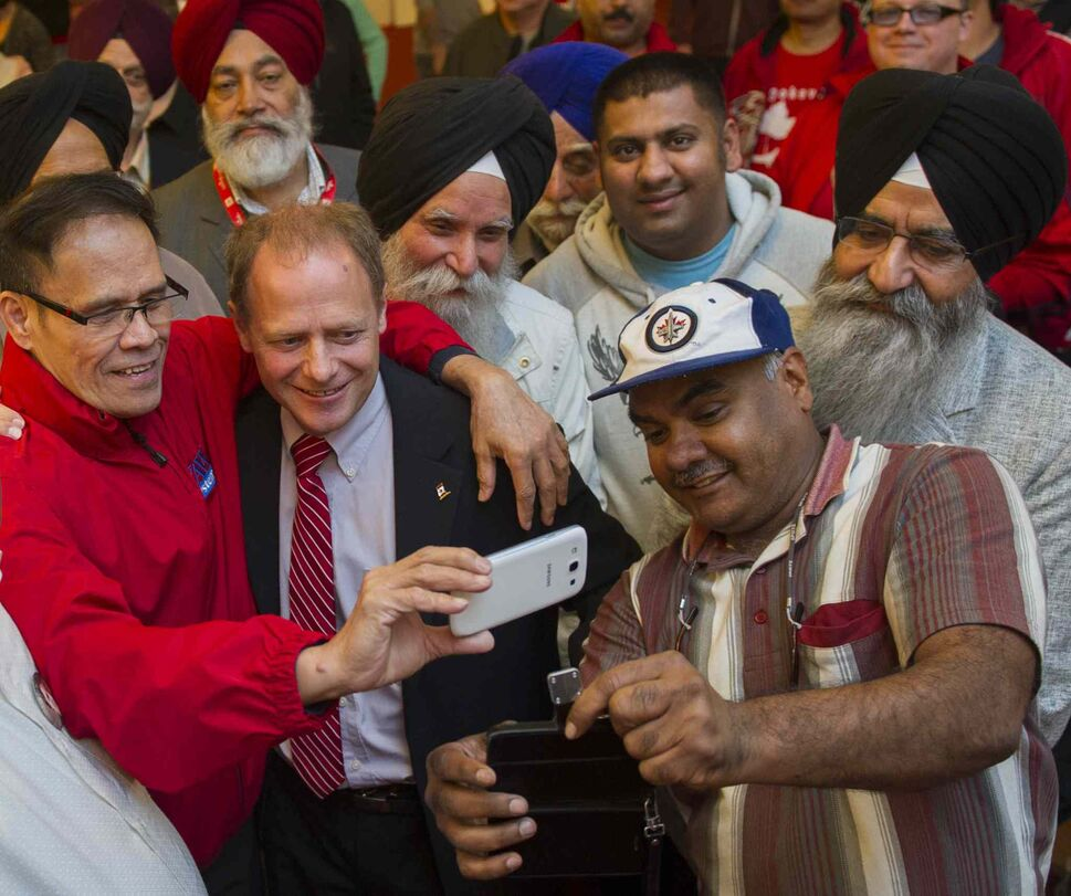 Incumbent Liberal Kevin Lamoureux (red tie) joins supporters at the Punjab Banquet Hall in his Winnipeg North riding Monday. (DAVID LIPNOWSKI / WINNIPEG FREE PRESS)