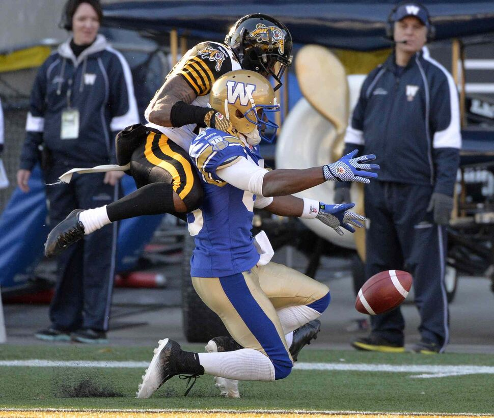 Hamilton Tiger-Cats' Arthur Hobbs (24) breaks up the pass in the end zone intended for Winnipeg Blue Bombers' Clarence Denmark (89) during the second half. (Fred Greenslade / The Canadian Press)